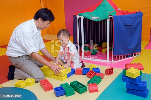 istock Asian father & cute little 18 months / 1 year old toddler baby boy child having fun playing with big colorful plastic building blocks indoor 1055380392