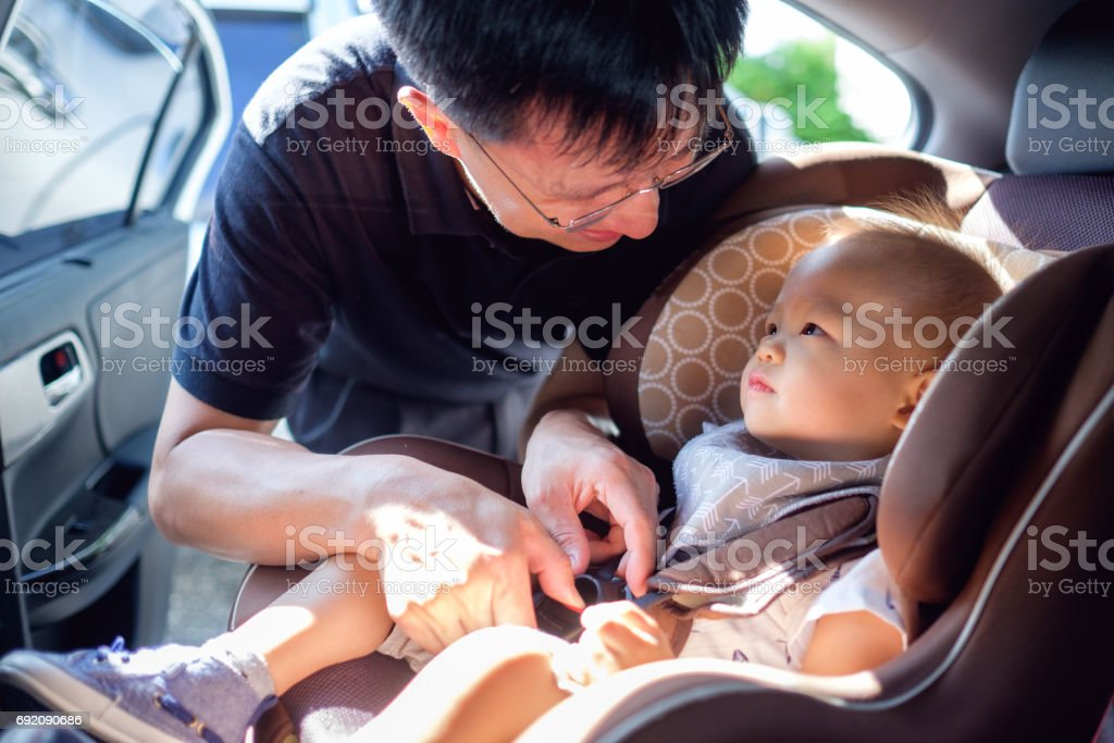 Asian father helps his cute little 1 year old toddler baby boy child to fasten belt on car seat in car stock photo