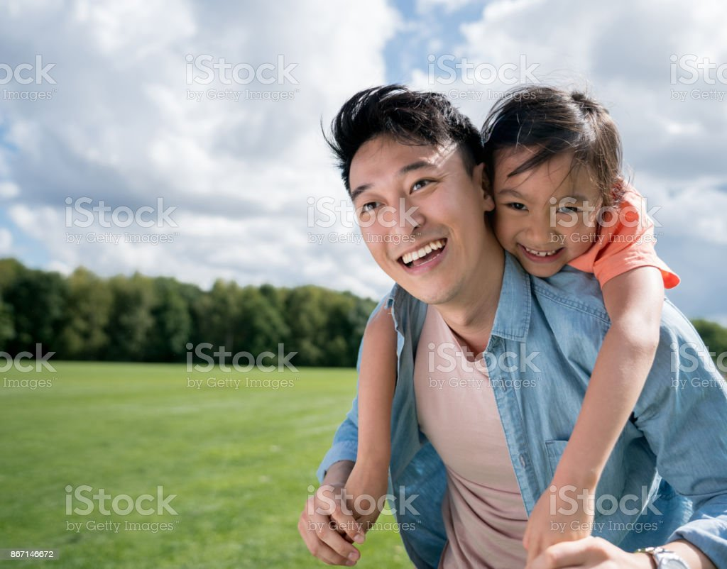Asian father looking very happy playing with his daughter at the park stock photo