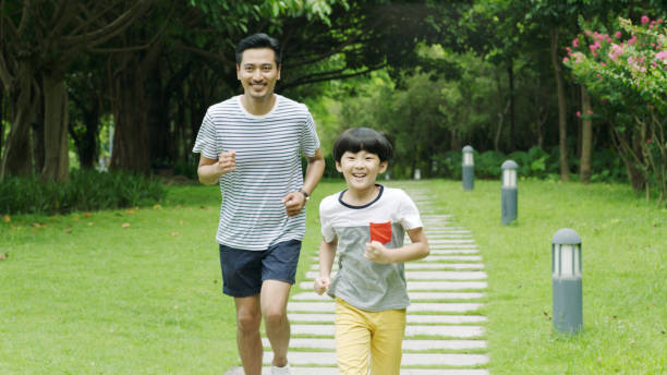 Asian father runing together with his little son in park in summer stock photo