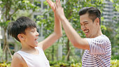 istock Asian father & son giving a high five after scoring outdoors in morning 898852104