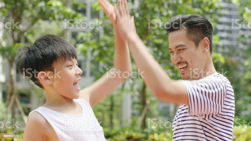 Asian father & son giving a high five after scoring outdoors in morning stock photo