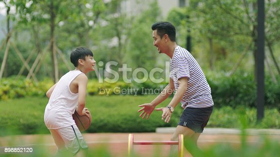istock Asian father & son playing basketball in garden in morning 898852120