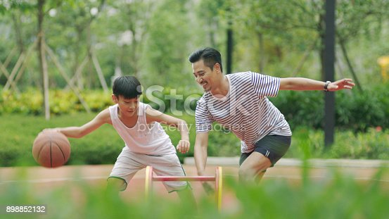 istock Asian father & son playing basketball in garden in morning 898852132