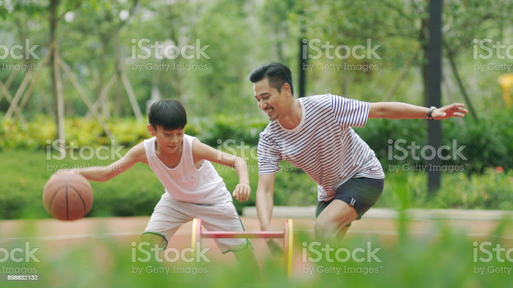 Asian father & son playing basketball in garden in morning stock photo