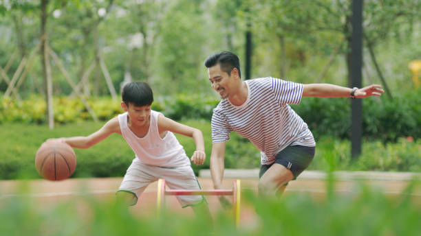 Asian father & son playing basketball in garden in morning - foto stock