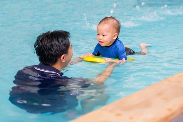 asiatischen vater nehmen niedlichen kleinen asiatischen 18 monate/1 jahr altes kleinkind baby junge kind schwimmen klasse - kindergarten workshop stock-fotos und bilder