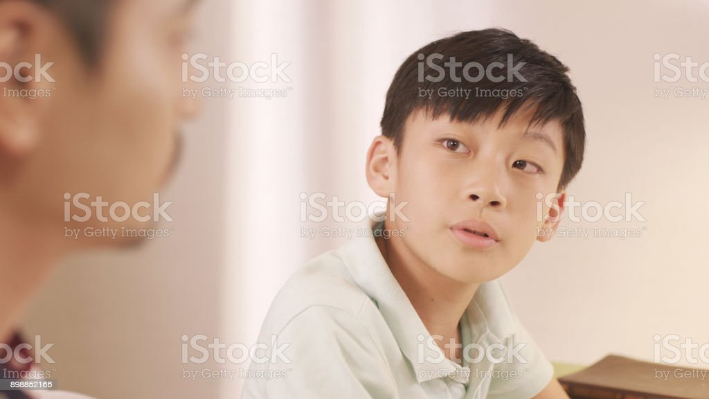 Asian father talking & counseling his frustrated teenage boy at home stock photo