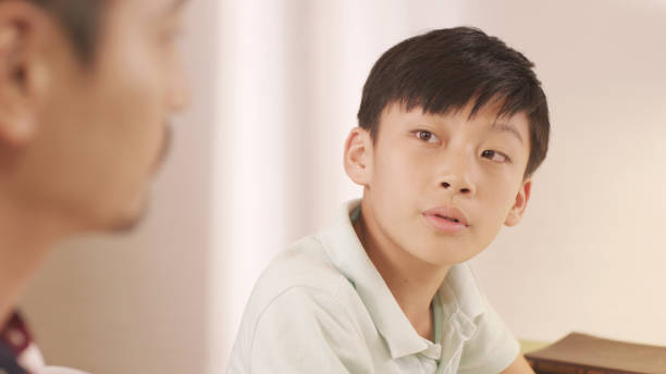 asian father talking & counseling his frustrated teenage boy at home - two students together asian foto e immagini stock