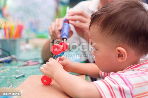 544351868 istock photo Asian Father teaching kid make a car toy with recycled materials, Little 2 years old toddler boy child make D.I.Y reuse toy with dad 1062570292