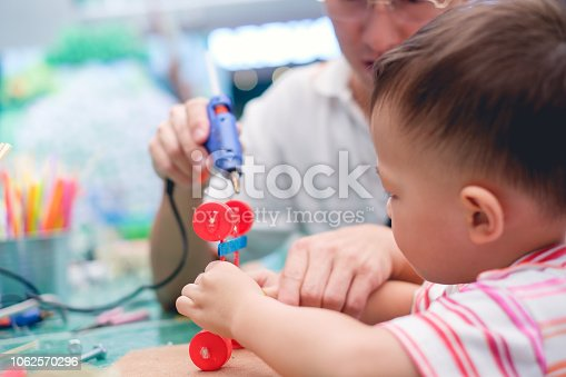 544351868 istock photo Asian Father teaching kid make car toy with recycled materials, Little 2 years old toddler boy child make D.I.Y reuse toy with dad 1062570296