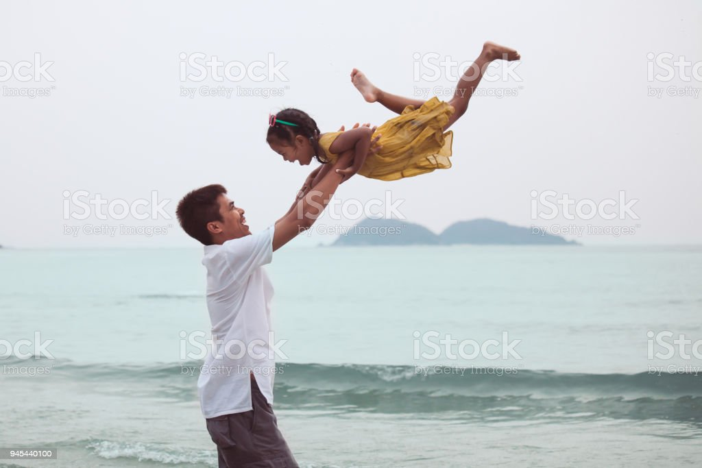 Asian father throwing his daughter up in the air and playing together in the sea stock photo