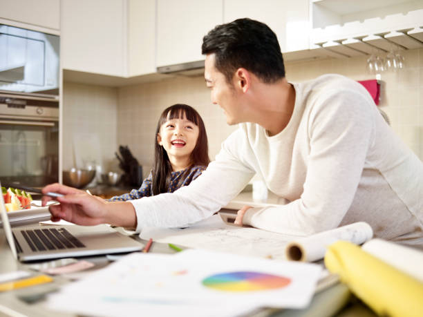 asian father working from home while caring for daughter stock photo