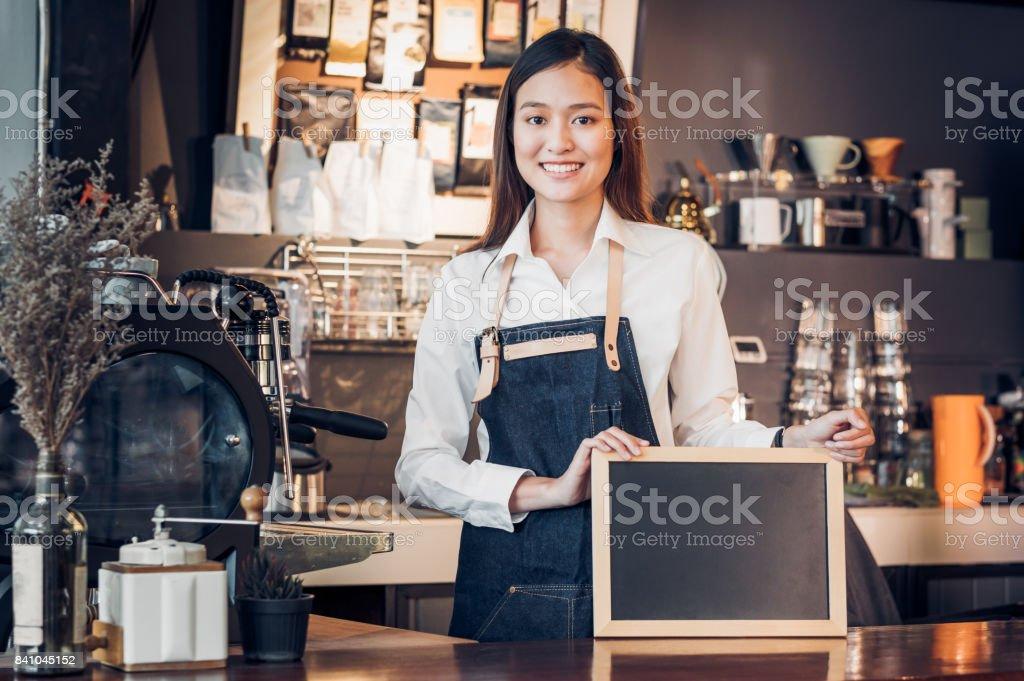 Asiatische Frauen Barista Verschleiß Jean Schürze und Holding leere Tafel Menü an Theke Bar mit Lächelngesicht, Café service Konzept, Inhaber Business Start-up, Mock für die Anzeige der Getränkekarte oder Text. – Foto