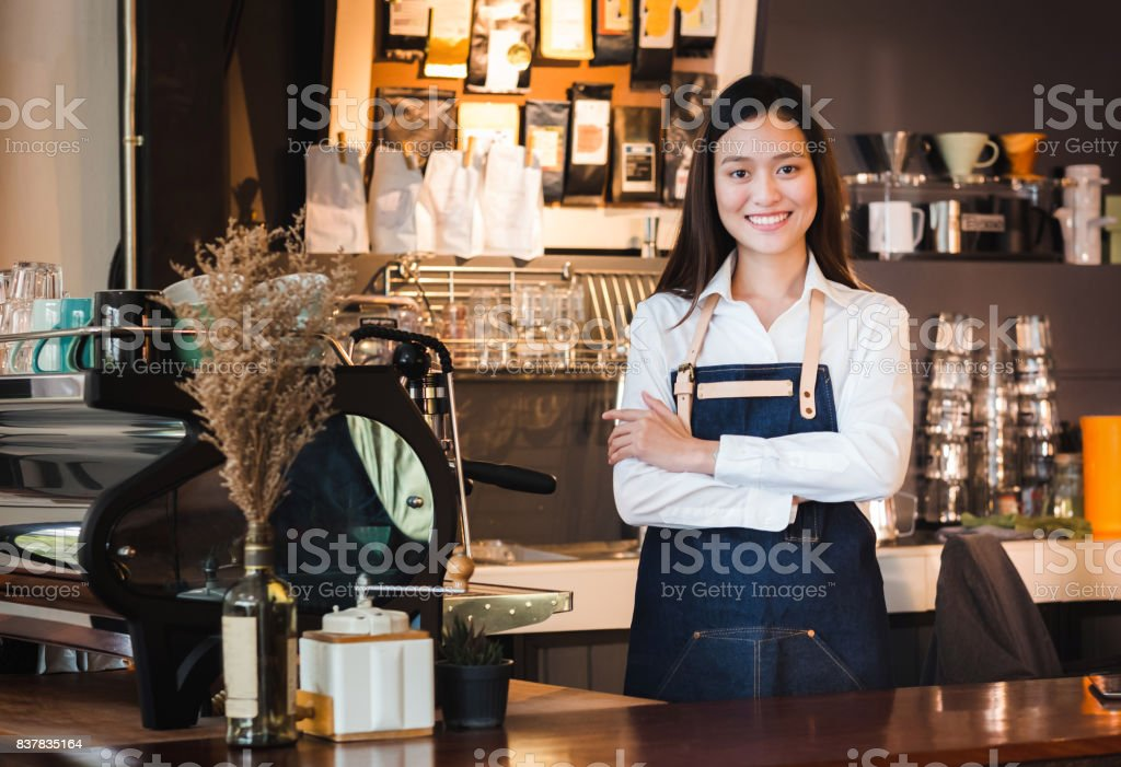 Asian female barista wear jean apron crossed her arms at counter bar with smile face,cafe service concept,owner business start up stock photo