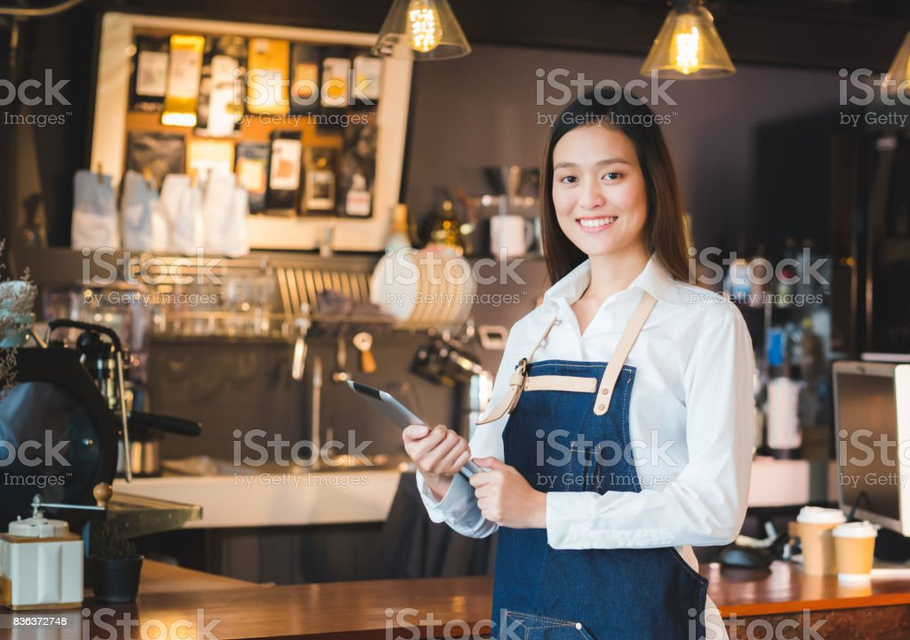 Asian female barista wear jean apron hold tablet computer coffee menu at counter bar with smile face,cafe service concept stock photo