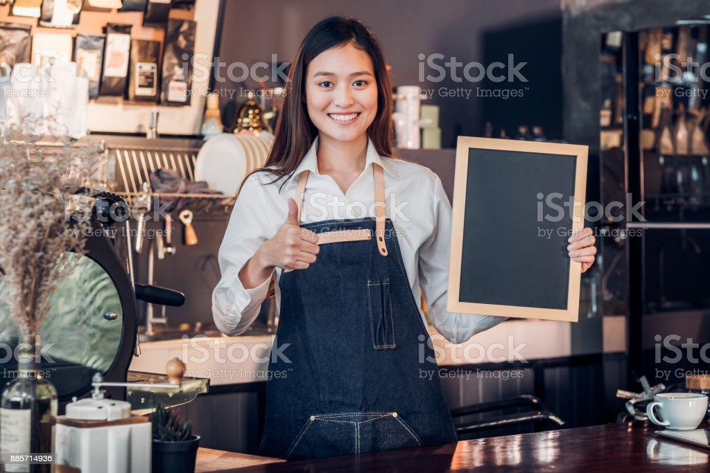 Asiatische Frauen Barista Verschleiß Jean Schürze Daumen hoch am leeren Tafel Kaffee Menü an Theke Bar mit Lächelngesicht, Café-Service-Konzept, Business Besitzer Start UpLeave Platz für Ihren Text hinzufügen... – Foto