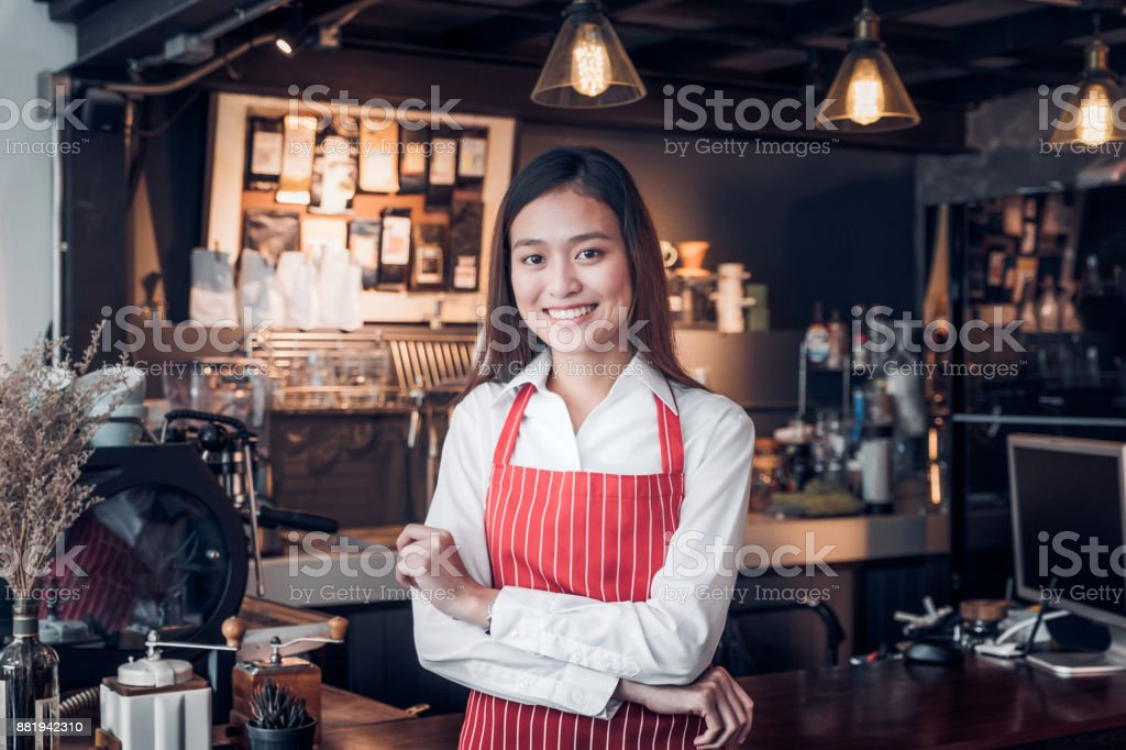 Asian female barista wear red apron crossed her arms at counter bar with smile face,cafe service concept,owner business start up stock photo