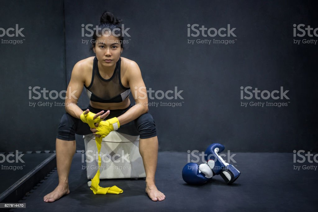 Asian female boxer wearing yellow strap on wrist and seeing boxing gloves on the floor stock photo