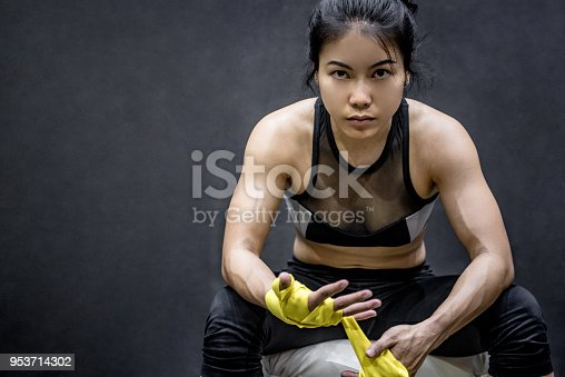 istock Asian female boxer wearing yellow strap on wrist 953714302