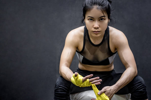 asiatique boxer femelle porte jaune bracelet poignet - boxe sport photos et images de collection