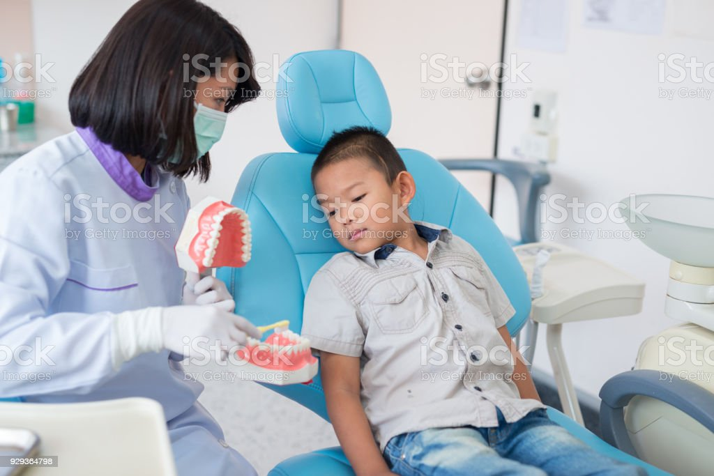 Asian female dentist talking to brush teeth properly explained to the boys were listening to in the hospital stock photo