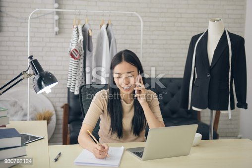 836871418 istock photo asian female designer talking on the phone while sitting at desktop with sketches of new clothes in her fashion-studio 930762124