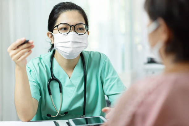 Asian female Doctor in green uniform wear glasses and surgical mask talking, consulting and giving advice to Elderly woman patient in medical room at the hospital. stock photo