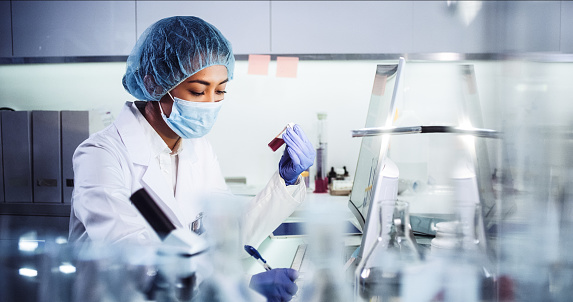 Asian female doctor working with pathogen samples. Using microscope