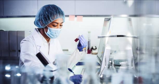 azjatycka kobieta lekarz pracujący z próbkami patogenów. za pomocą mikroskopu - laboratorium zdjęcia i obrazy z banku zdjęć