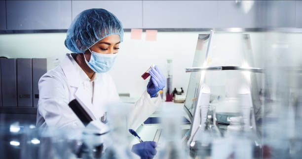 Asian female doctor working with pathogen samples. Using microscope Young woman during virus lab tests microbiologist stock pictures, royalty-free photos & images