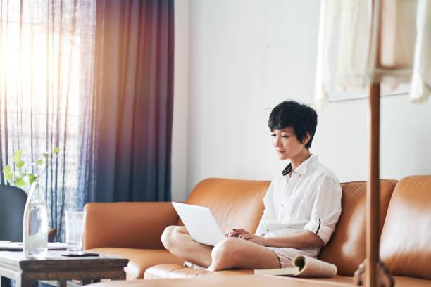 アジアの女性フリーランサーが自宅でノートパソコンに取り組んで ストックフォト