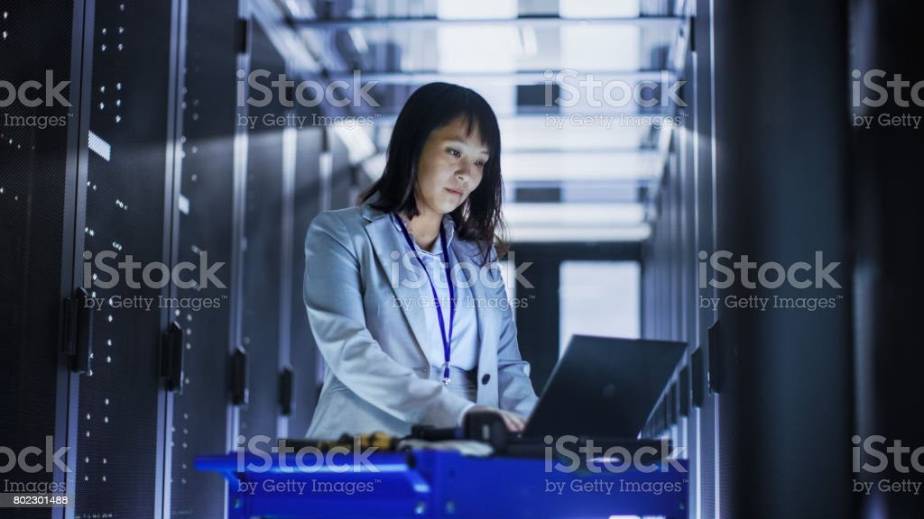 Asian Female IT Engineer Working on a Laptop on Tool Cart, She Scans Hard Drives.  She's in a Big Data Center Full of Rack Servers. stock photo