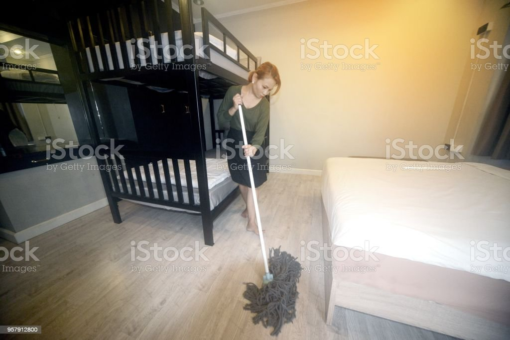 Asian female maid cleaning service with Mop cleaning floor inside a...