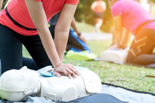 Asian female or runner woman training CPR demonstrating class in park by put hands and interlock finger over CPR doll give chest compression. First aid training for heart attack people or lifesaver. stock photo