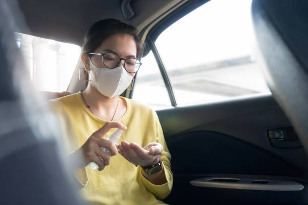 Asian Female Passenger in green or yellow shirt and protective mask spraying disinfectant alcohol on her palms and her hands for prevent coronavirus or Coronavirus while her in a car. stock photo