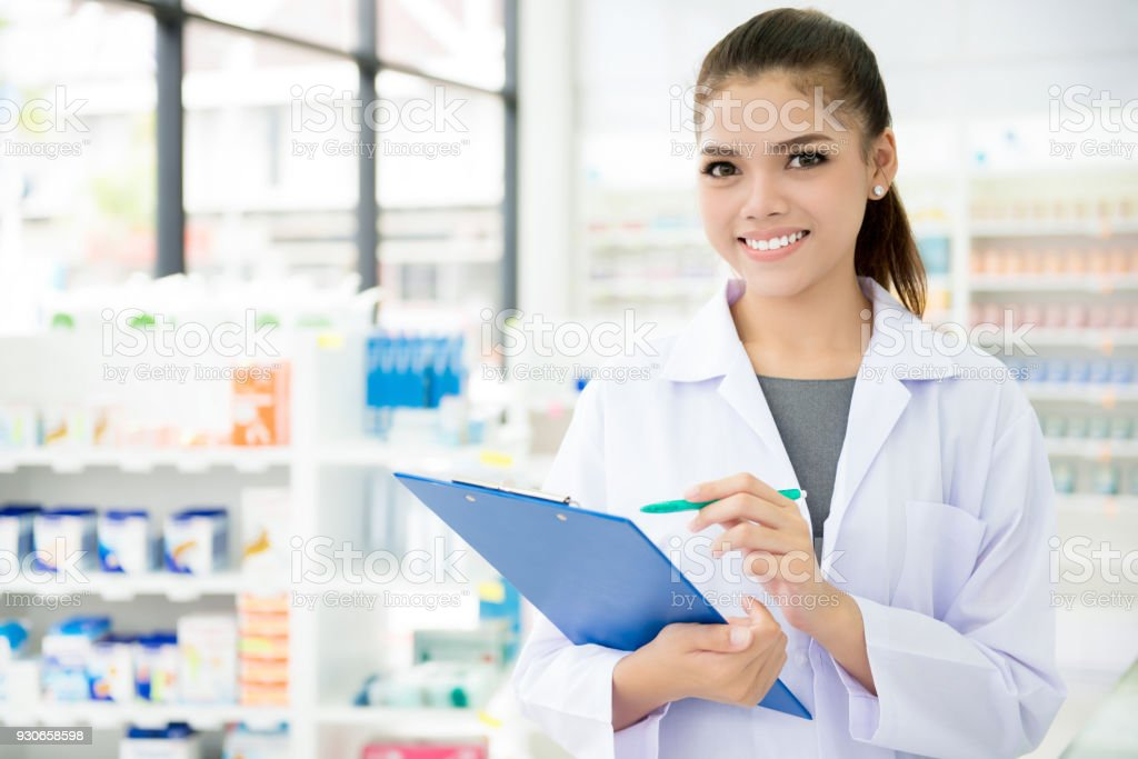 Asian female pharmacist working in chemist shop or pharmacy stock photo