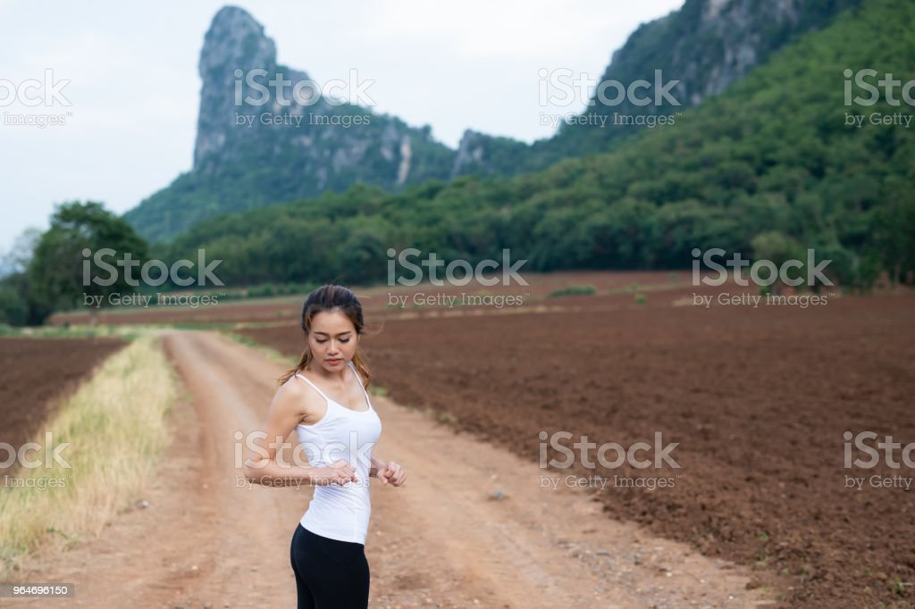 Asian female runners are stretching muscles before exercise. jogging on mountain road. The concept of health and fitness royalty-free stock photo