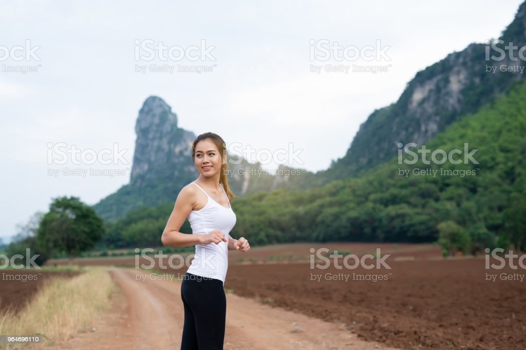Asian female runners smile are stretching muscles before exercise. jogging on mountain road. The concept of health and fitness royalty-free stock photo