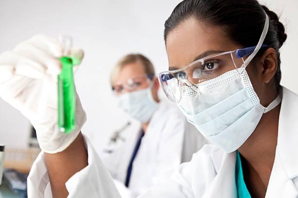 Asian científica femenina con tubo de ensayo de laboratorio solución verde - foto de stock