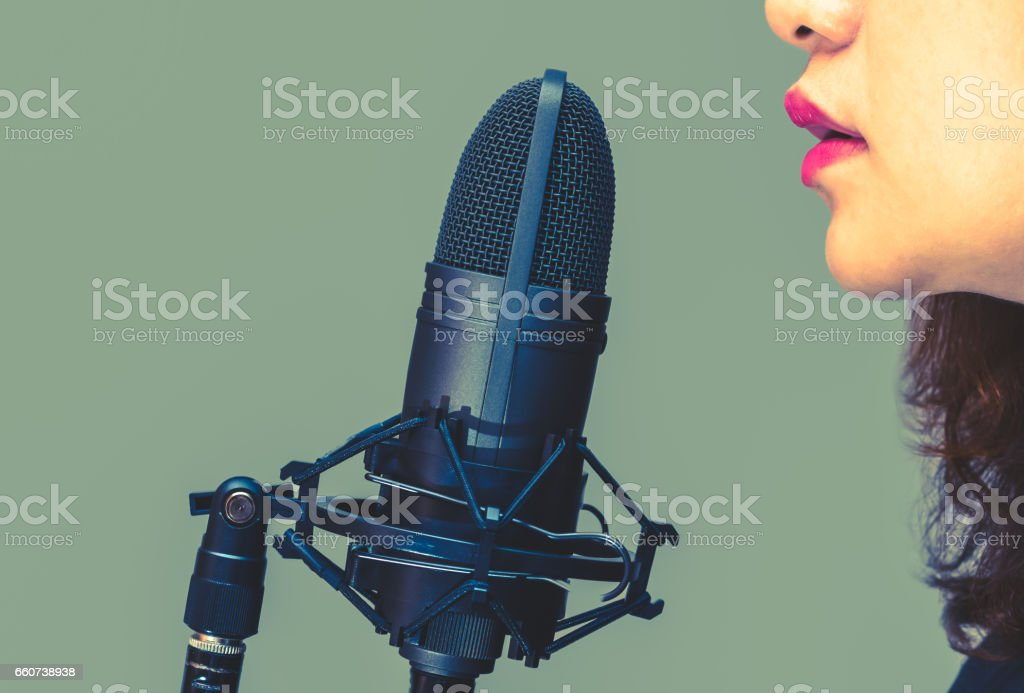 asian female singer mouth singing on microphone stock photo