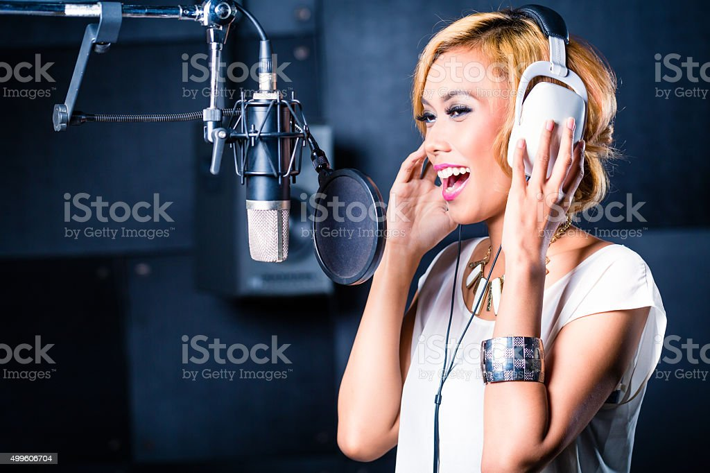 Asian female singer producing song in recording studio stock photo