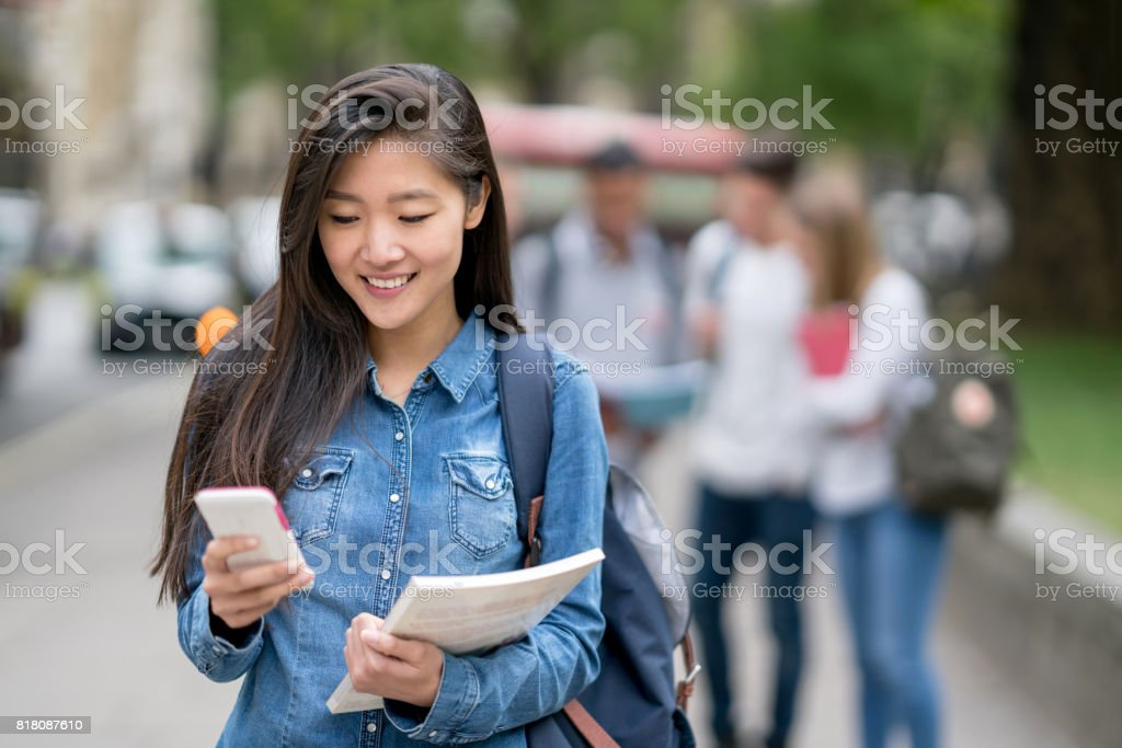 Asian female student texting on her mobile phone outdoors stock photo