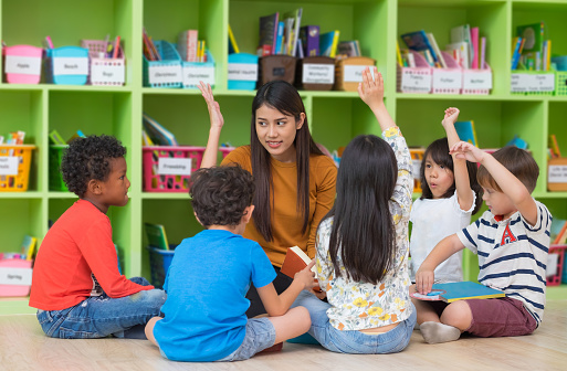 istock Asian female teacher teaching and asking mixed race kids hand up to answer in classroom,Kindergarten pre school concept. 1051078690