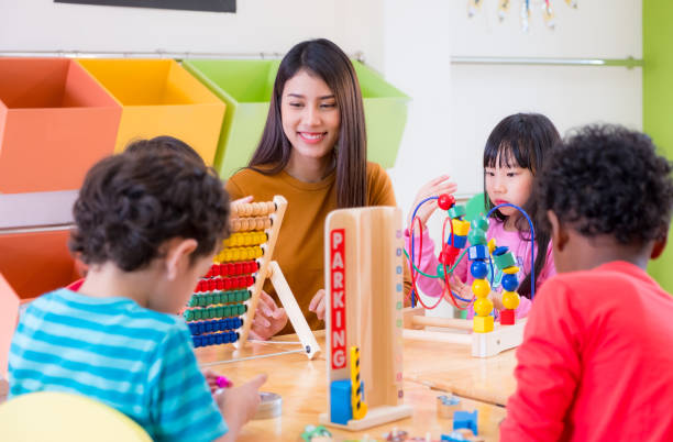 Asian female teacher teaching mixed race kids play toy in classroom,Kindergarten pre school concept stock photo