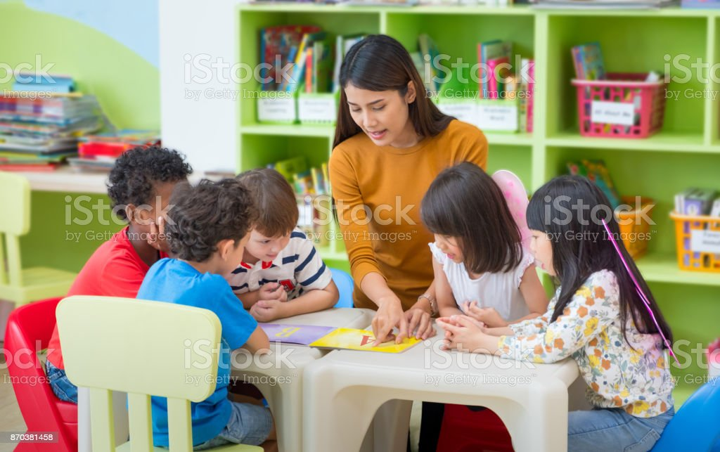 Asian female teacher teaching mixed race kids reading book in classroom,Kindergarten pre school concept. stock photo