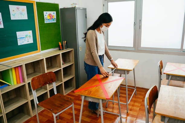 Asian female teacher wearing a face mask measures distances between desks in classroom in primary school.