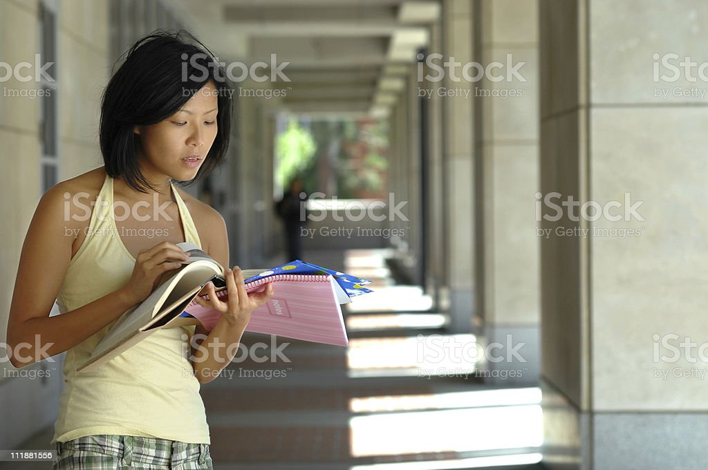 Asian Female University Student Studying from Textbook on College Campus stock photo