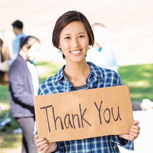 Asiatique femme bénévole tenant Merci de plein air - Photo