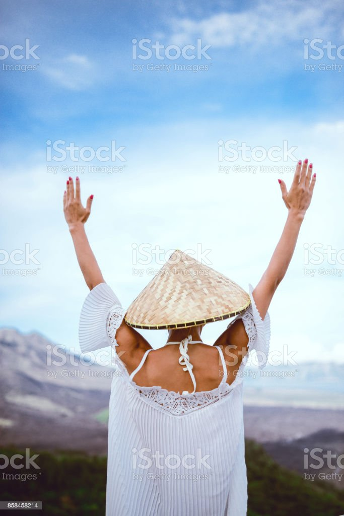 Asian Female wearing Traditional Straw Hat Praying with Raised Hands stock photo